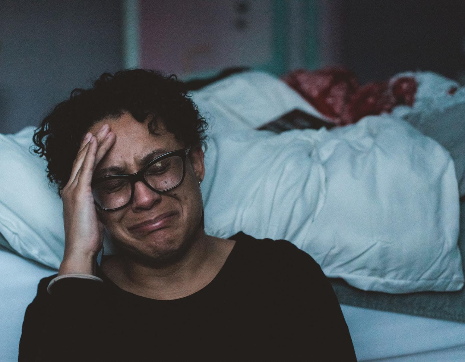 30 year old african / asian woman leaning against a bed and crying