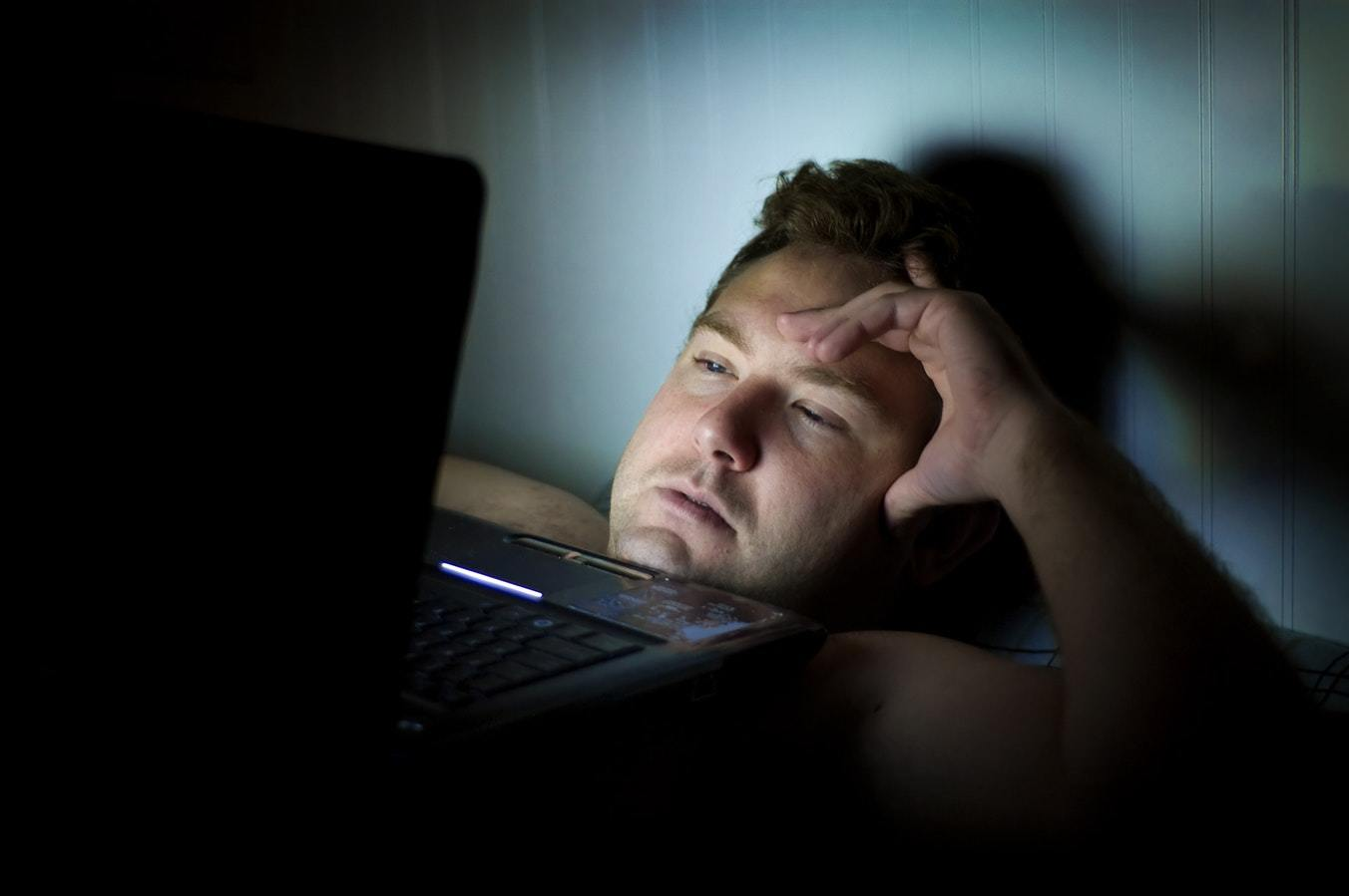 man lying in bed staring at laptop and looking worried