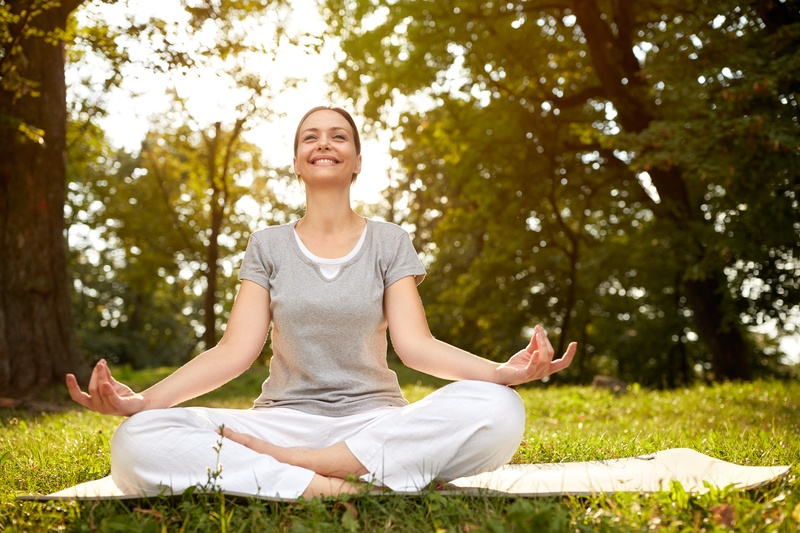 Cheerful woman in lotus pose meditate in green park