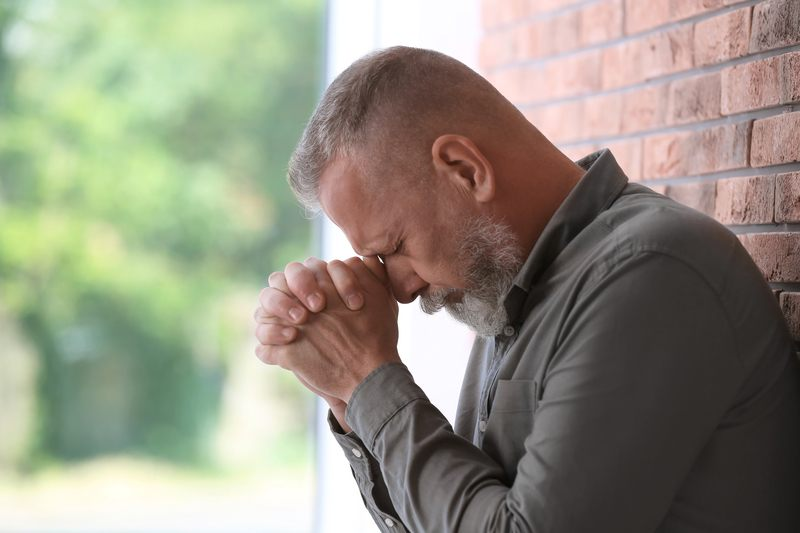 Senior man in state of depression near brick wall