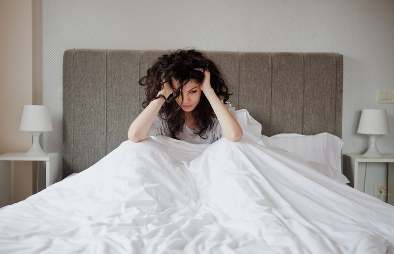 Woman is stress in bed and having some mental health issues